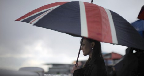 LIVERPOOL, ENGLAND - APRIL 13:  A racegoer shelters from the rain under a large Union Jack umbrella during Ladies Day at the Aintree Grand National meeting on April 13, 2012 in Aintree, England. Friday is traditionally Ladies day at the three-day meeting of the world famous Grand National, where fashion and dressing to impress is as important as the racing.  (Photo by Christopher Furlong/Getty Images)